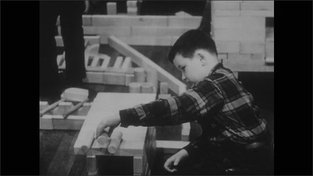 1960s: Boy hands blocks to other boy. Boy stacking blocks. Boy moving blocks on structure.