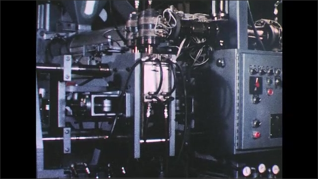 UNITED STATES 1950s: Plastic molding machine forms bottles, worker takes bottles.