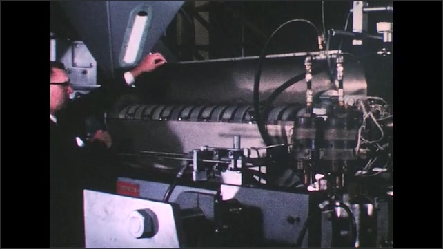 UNITED STATES 1950s: Plastic molding machine, man lifts piece of equipment, zoom in on equipment.