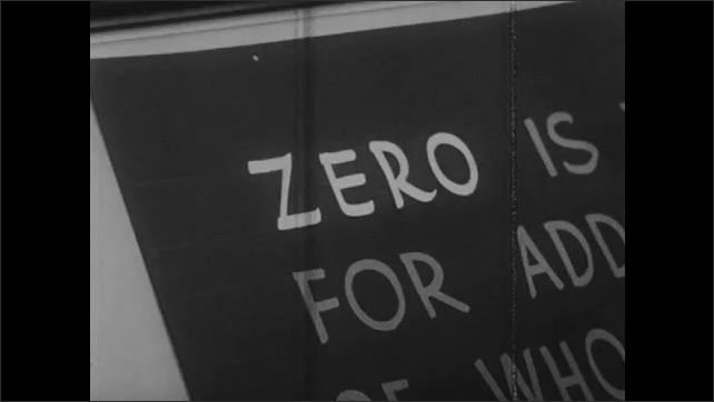 1960s: Man does hand lettering on large board.
