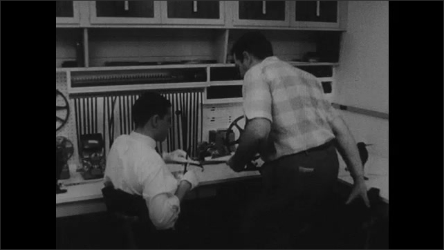 1960s: Film editor looks at strips of film at editing station. Man approaches editor with clipboard, they talk while looking over notes.