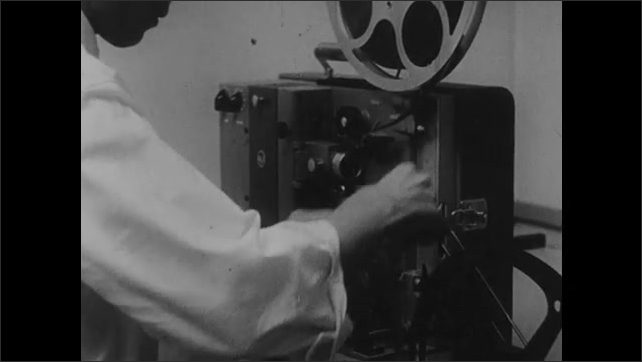 1960s: Man loads film projector and turns it on.