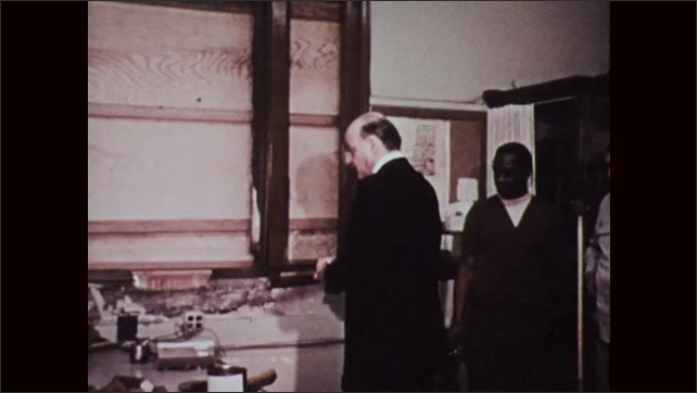 1970s: Broken window. Staple lodged into wall. Man flips through damaged book. Man looks over damage to officer.