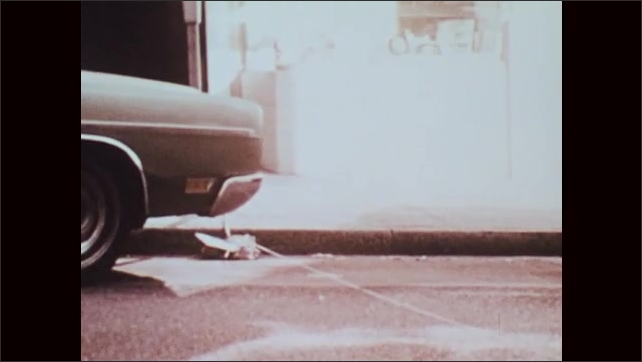 1970s: Policemen tie string to package attached to parking meter, walk away and pull sting. Package falls apart.