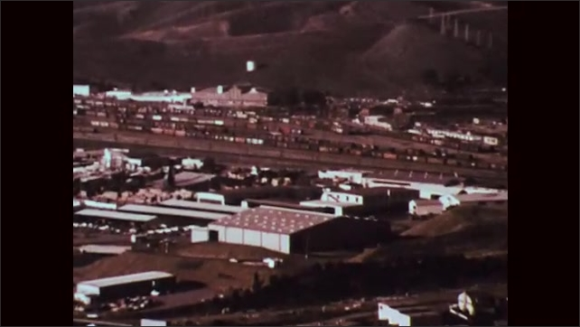 1970s: Cars travel on freeway around city. Railroad freight yard. Train travels on tracks.