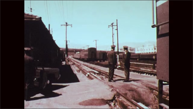 1970s: Policemen stand on train tracks. Policemen talk and point. Train pulls into station.