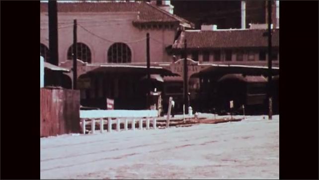 1970s: Two policemen talk. Policeman talks into car radio. Policecar drives through lot.
