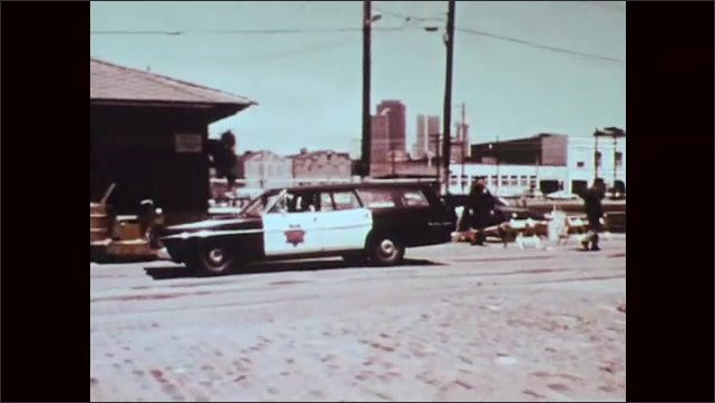 1970s: Clock. Police car drives across lot. Policemen exit car, remove bags from back of car, walk towards trainyard.