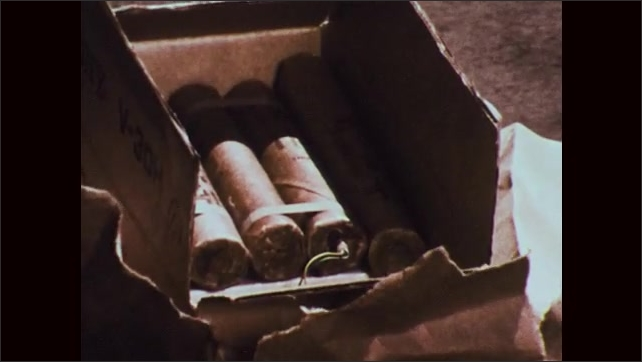 1970s: Partially opened package on ground. Policeman looks up. Bomb component. Inside of bomb.