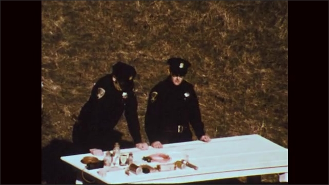 1970s: Policemen stand outside at table with bomb components on it. Policeman talks.