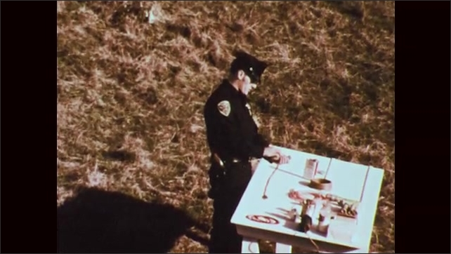 1970s: Policeman stand outside at table with bomb components on it. Policeman talks, pours powder into hand, places powder on table, walks away from table.