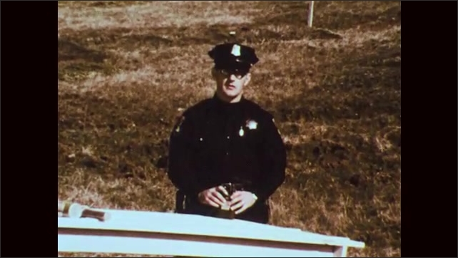 1970s: police officer standing behind table talking to crowd