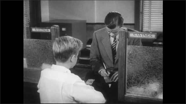 UNITED STATES 1950s: Boy walks to counter in bank / Boy gives man money over counter/ Man sorts through files