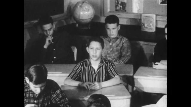 1950s: Students sit in classroom.  Boy speaks.  Teacher stands.