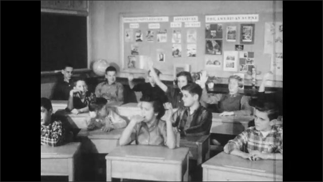 1950s: Students sit in classroom.  Boys and girls raise hands.