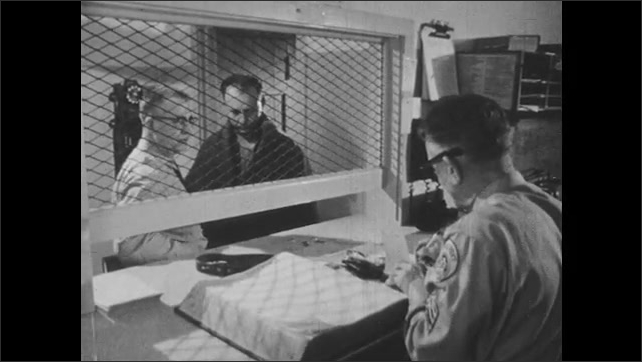1950s: Police officer talks to man while second officer writes a receipt. Officer escorts man through door.
