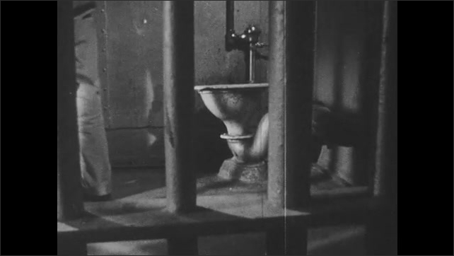 1950s: police officer in uniform sits, smokes cigarette and writes in ledger at desk. legs pace in jail cell near toilet in New Orleans jail. cops walk into hallway of cellblock.