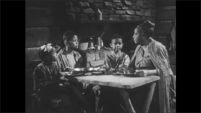 1940s: Slave family sits at table. Woman speaks to children at table. Children respond to woman. Women and children speak at table.
