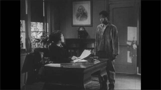 1940s: Boy enters office. Boy approaches desk and speaks to woman. Boy and woman talk. Man enters office and speaks. Boy responds.