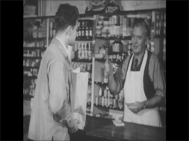 1950s: UNITED STATES: Man serves customer in store. Hand writes receipt on paper. Man puts groceries on tab. Workers in store. Man gives cash to worker