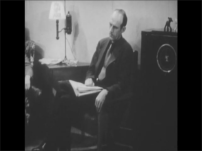 1950s: UNITED STATES: man reads notes to microphone. Man listens to radio in house. Man sits in chair. Voters listen to radio news