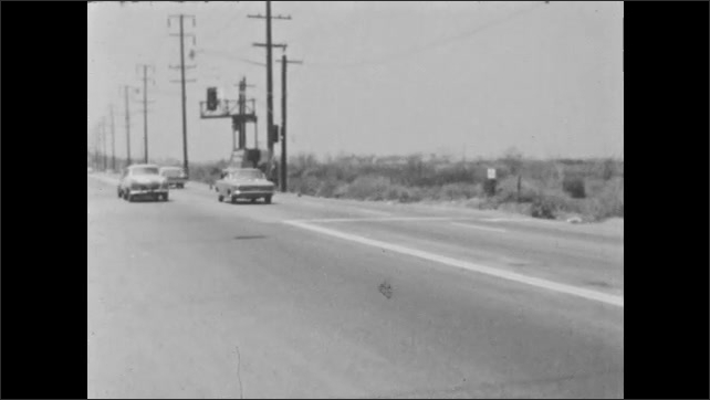 1960s: Young man sticks head out window of car, drives off. Man driving, man scrunches up face, continues driving.