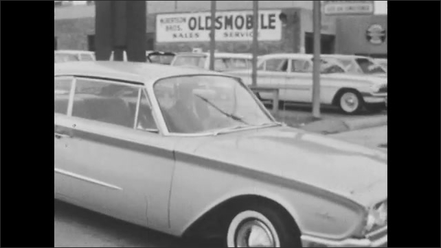 1960s: Man puts key in car ignition, misses key slot first time. Car pulls out of parking lot. Car drives down street, another car pulls in front, nearly T-bone collision.