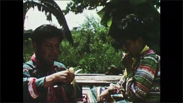 1950s: father cutting banana for son to eat