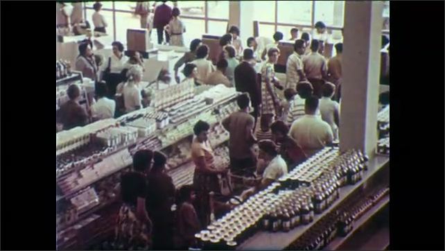 1950s: Building.  People shop in supermarket.  Woman rings up groceries.  People walk past church.