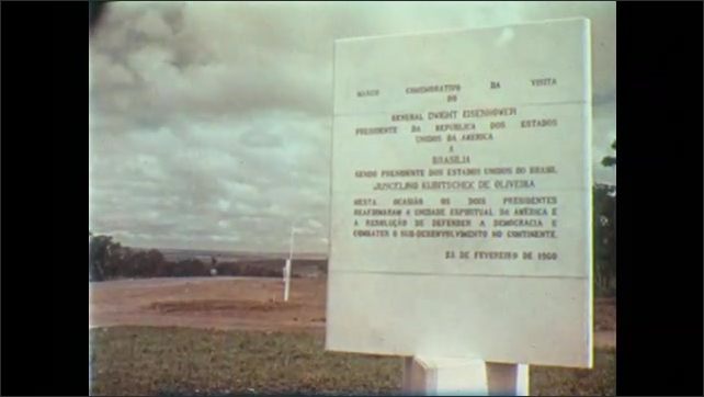 1950s: Row of flags wave.  Sign.  Truck drives through field.
