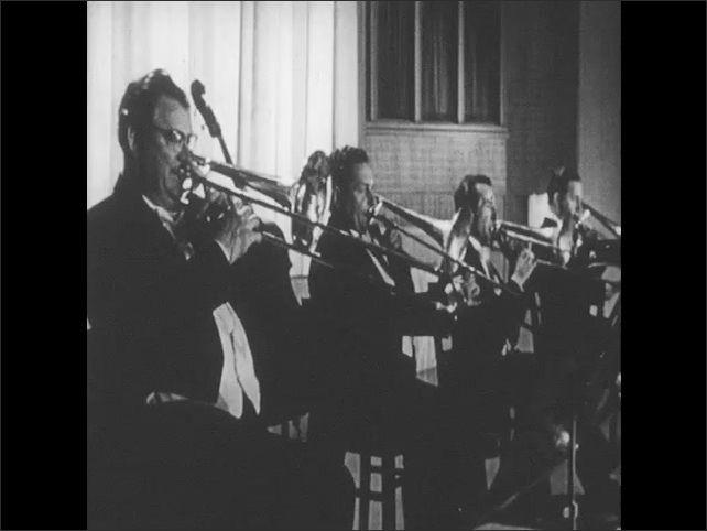 1950s: UNITED STATES: close up of French Horns. Men play trombones in concert. Man plays trumpet. Hands press keys on trumpet