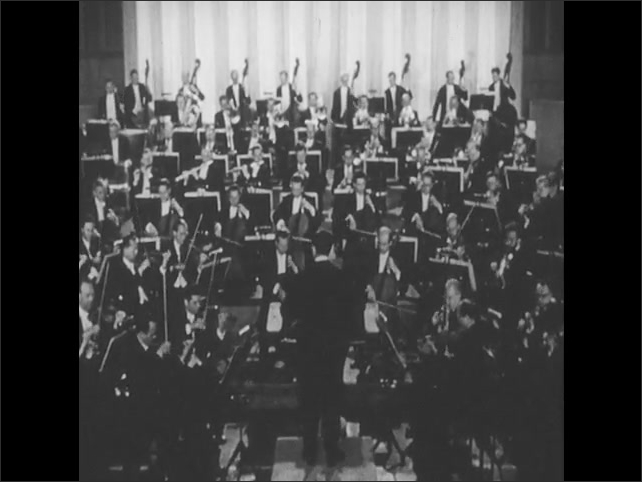 1950s: UNITED STATES: man conducts string section in concert. Conducts stands in front of orchestra