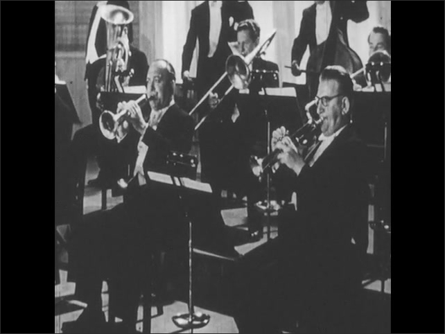 1950s: UNITED STATES: brass section play in orchestra. Woodwind section in orchestra. Man conducts orchestra