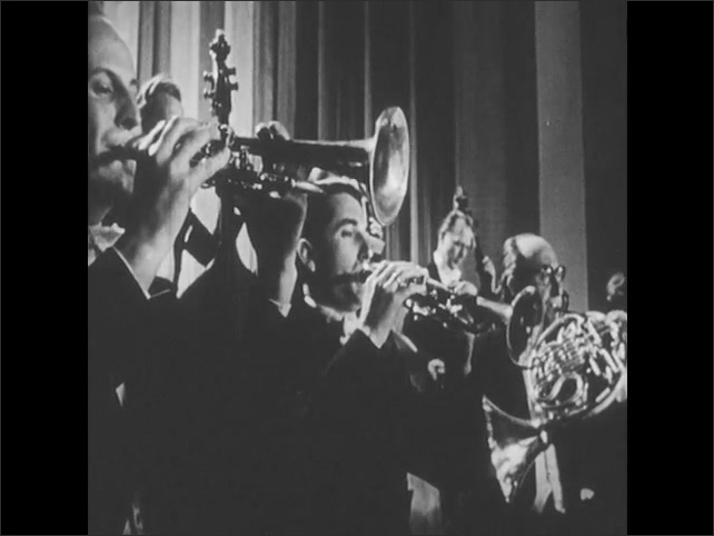 1950s: UNITED STATES: brass section of orchestra. Men plays brass instruments in concert