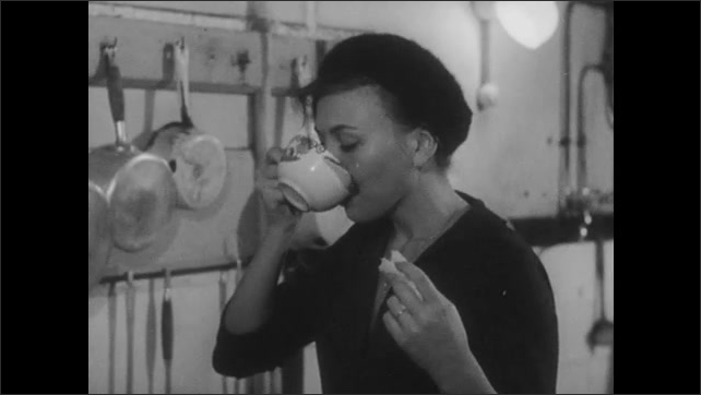 1960s: Kitchen.  Woman pours tea and drinks.  Woman eats bread.