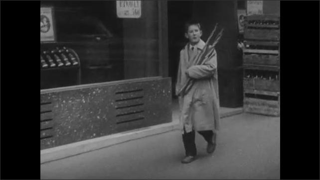 1960s: City street.  People walk along carrying bread.  Man eats.