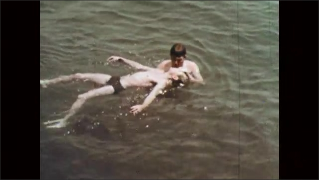 1960s: UNITED STATES: man does mouth to mouth breathing to boy in sea. Boy blows up ball