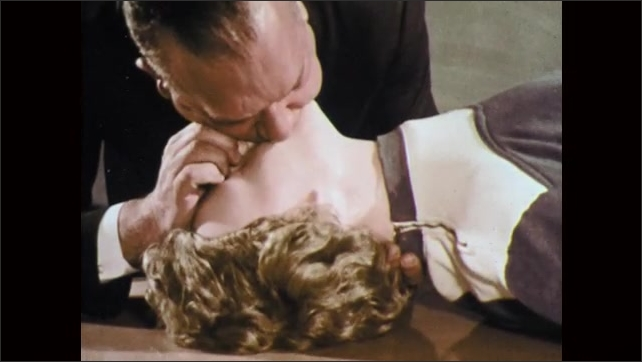 1960s: UNITED STATES: girl in classroom. Training mannequin in classroom. Man seals nose of mannequin and performs CPR. Chest rises on mannequin.