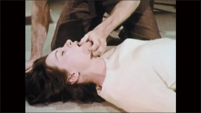 1960s: UNITED STATES: lady with object stuck in throat. Man turns lady over and slaps between shoulder blades. Man clears throat with fingers. Man pinches victim's nose.