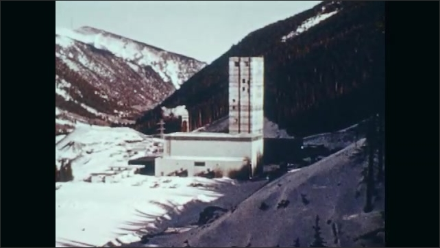 1970s: Snowy mountains.  Building.  Miners ride down in elevator.