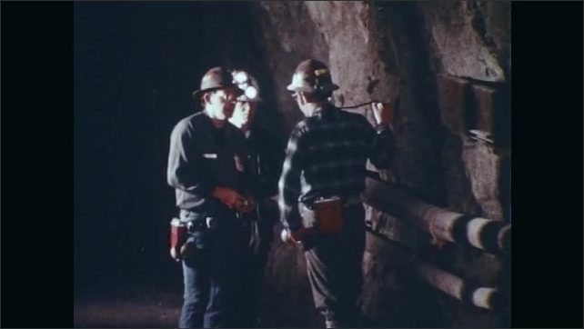 1970s: Mine.  Smoke blows through tunnel.  Men stand and wait.  Miners sit at table and eat lunch.