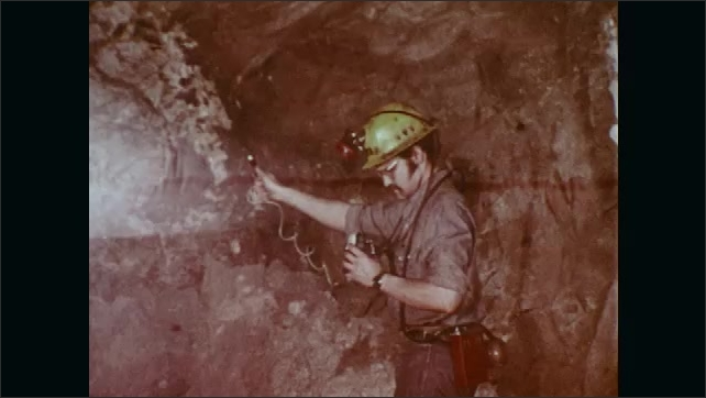 """1970s: Mine.  Tool blows dust into air.  Man tests air in tunnel.  Man ducks under fence with sign reading """"DANGER.  KEEP OUT.""""  Ventilation tubing."""