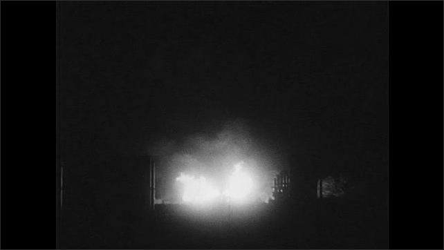 1940s: Close up of corn burning. Man stokes fire. Close up of corn burning. Long shot of fire. Fire, silhouette of factory. Factory lights. Factory at night. Men working on scaffolding.