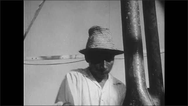 1940s: Pan across forest to oil rig. Close up of man. Drill lowering. Hands pull off metal pieces. Man with drill. High angle view of well. Man next to drill. Mud spraying.