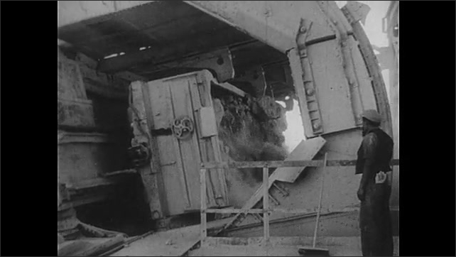 1940s: View of explosion in empty field. Man next to rotating machine. Pan of train driving.