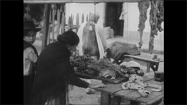 1940s: Man carries item from horse to vendor table at outdoor market. Woman in hat. Woman looking at vendor