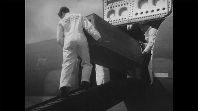 1940s: Men and crane load large crate into aircraft. Men load boxes onto plane. Man drives mobile crane towards plane.