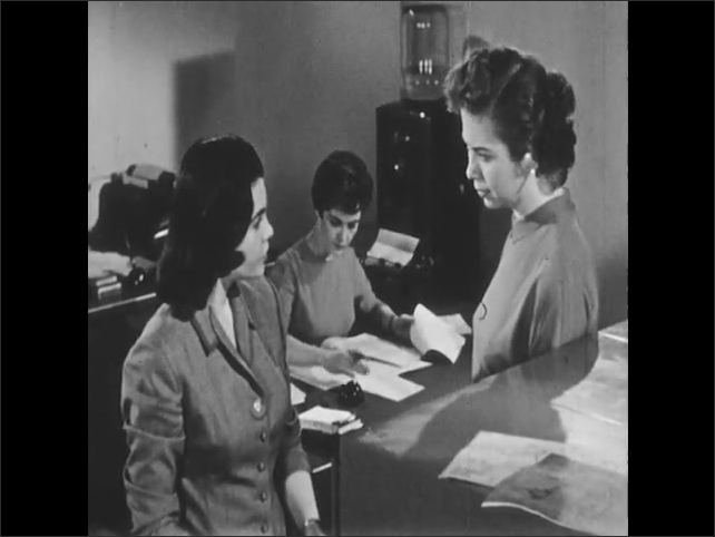 1950s: UNITED STATES: lady looks through files in cabinet. Ladies speak by files.