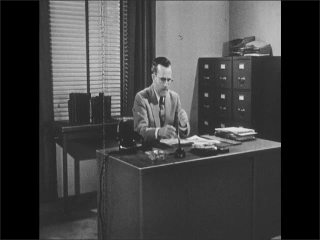1950s: UNITED STATES: man speaks on telephone at desk. Man puts down phone. Man thinks to self. Man taps pencil on desk