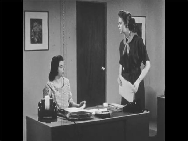 1950s: UNITED STATES: ladies speak in office. Lady reprimands girl at desk